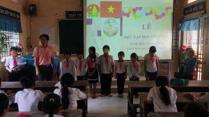 Thầy Lê Ngọc Lức -TPTĐ đeo khăn quàng cho học sinh